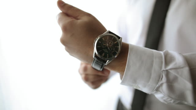 Young man adjusting wristwatch while standing near window in hotel room video