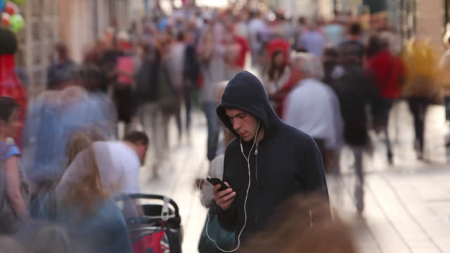 Young Man Alone in Busy Street Young Man Alone in Busy Street with Motion Blurred Persons hacker stock videos & royalty-free footage