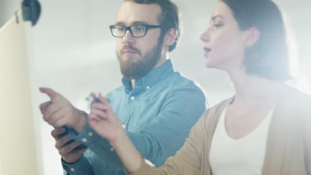 Jeune homme et une femme discutent de processus de travail sur un tableau blanc. L'homme détient Smartphone. Femme s'appuie sur un tableau blanc. - Vidéo