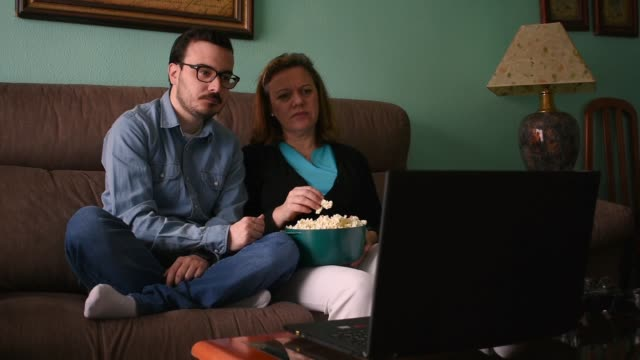 vídeos de stock e filmes b-roll de a young man and his mother watch a movie on the laptop in the living room - tv e familia e ecrã
