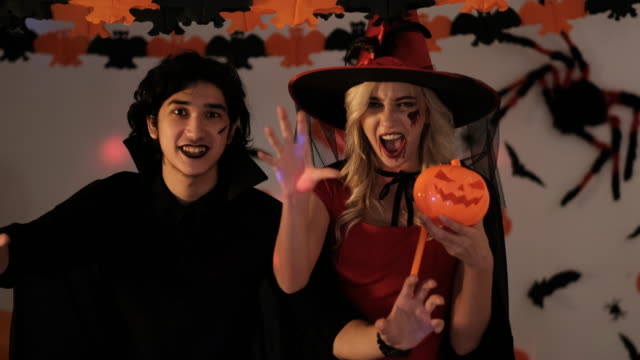 Young man and woman action for scaring to camera with Halloween concept at night. Halloween known as All Hallows Eve, or All Saints Eve, is celebration observed in many countries on 31 October