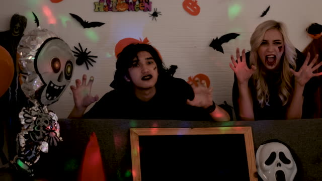 Young man and woman action to scare with Halloween concept at night