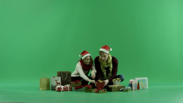 若い男と女の買い物袋の中で何かを探している背景にクロマキー - サンタの帽子点の映像素材/bロール