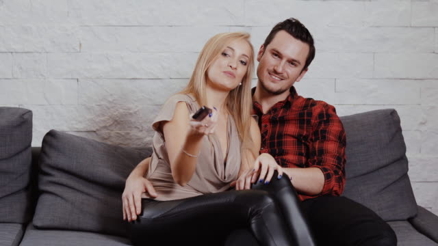 young man and woman are sitting on the couch, watching TV and holding a remote video