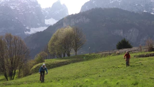 vidéos et rushes de bicyclette de jeune homme et de femme à travers la prairie verte, sous les montagnes - évasion du réel
