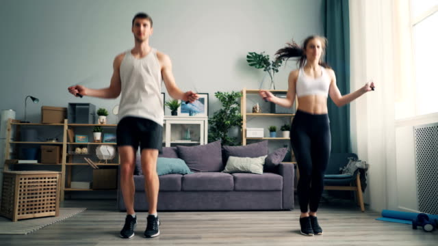 Young man and woman couple jumping rope in house together doing sports indoors Young man and woman beautiful couple is jumping rope in house together doing sports indoors focused on practice. People, active lifestyle and relationship concept. healthy lifestyle stock videos & royalty-free footage