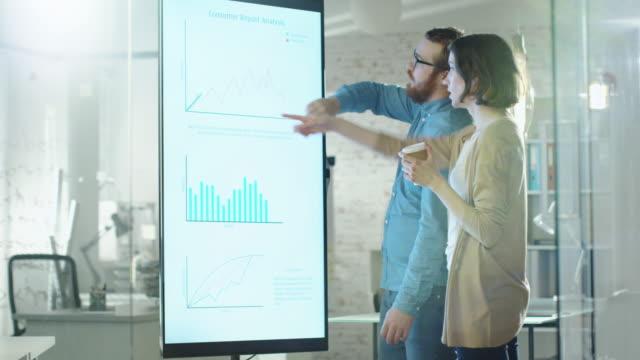 Femme et jeune homme discutent graphiques dessinés sur leur tableau blanc électronique. Homme montre plus de détails sur l'écran femme écoute Holding tasse de café dans son bureau de Hands.Their est développeur et moderne à la recherche. - Vidéo