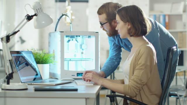 Jovem e mulher engenheiros criam modelos usando impressora 3D. - vídeo