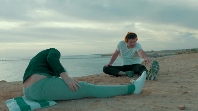 Young man and woman exercising by the sea video