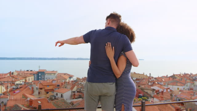 Young man and woman holding each other on the walkway above a picturesque coastal town and enjoying the view