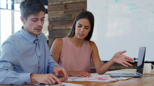 Young man and woman in discussion in a creative office video