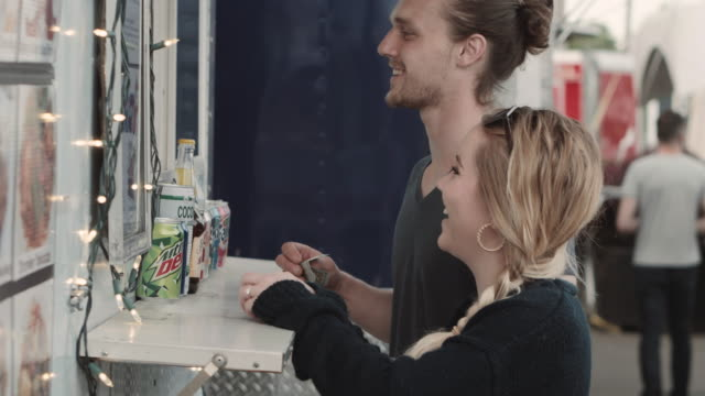 genç erkek ve kadın bir gıda kamyon tezgahta yemek siparişi - sipariş vermek stok videoları ve detay görüntü çekimi