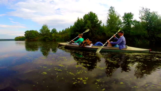 Young man and woman paddling boat, active rest, slowmotion video