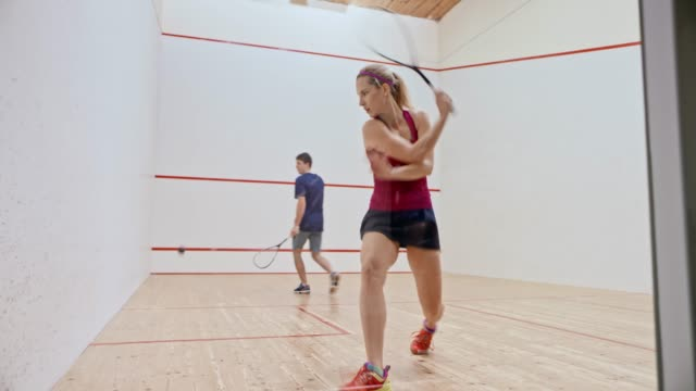 DS Young man and woman playing squash