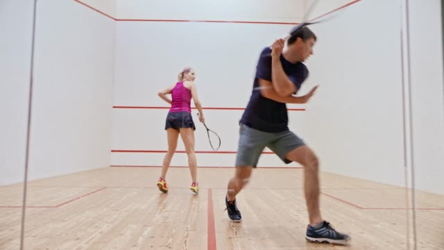 LD Young man and woman playing squash Wide locked down shot of a young man and woman playing a game of squash. Shot in Slovenia. hobbies stock videos & royalty-free footage
