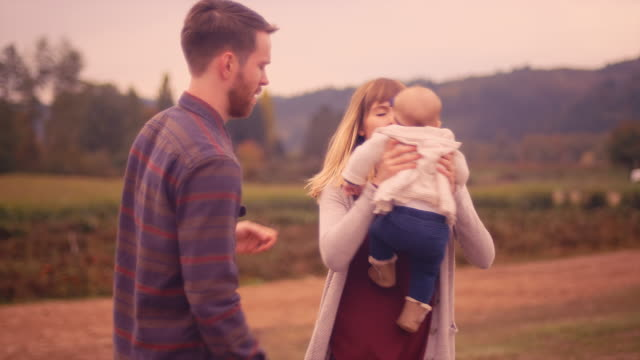 A young man and woman putting their baby into a wagon at a pumpkin patch