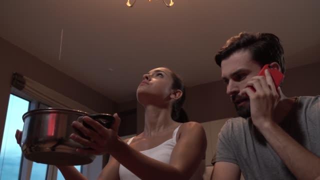 若い男と女が座っています。両者が見上げます。女の子は、手でポットを保持しています。天井から水が漏れています。彼女は心配しています。男は携帯電話で話しています。彼は同様に心� - 屋根点の映像素材/bロール