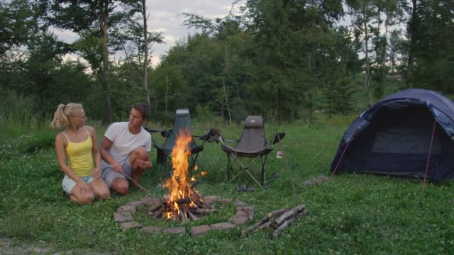 COPY SPACE: Young man and woman sitting by campfire get irritated by pesky bugs.