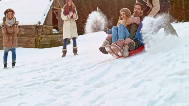 slo mo young man and woman sitting on a sledge being pushed down the hill by a male friend - slitta video stock e b–roll