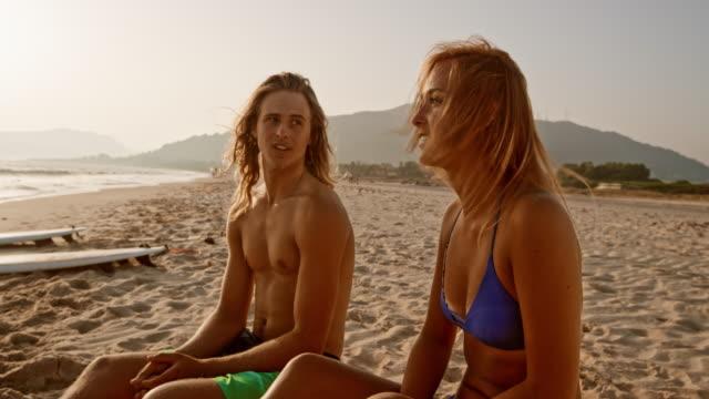 junger mann und frau am strand zu sprechen, als die sonne untergeht - nackter oberkörper stock-videos und b-roll-filmmaterial