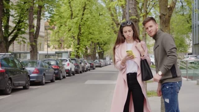 vidéos et rushes de jeune homme et femme utilisant son application de smartphone pour trouver le covoiturage - homme faire coucou voiture