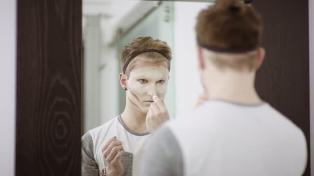 stockvideo's en b-roll-footage met jongeman toepassing van make-up voor spiegel - drag queen