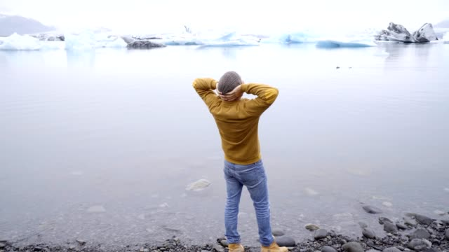 Young man arms outstretched at glacier lagoon in Iceland enjoying freedom in nature. Cold weather travel fun arms outstretched adventure concept 4K