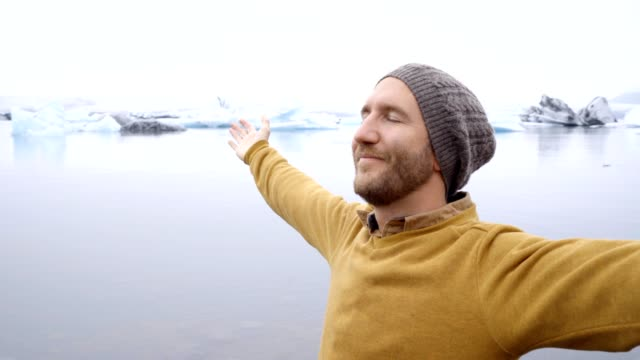 Young man arms outstretched at glacier lagoon in Iceland
