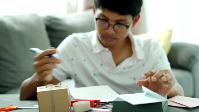 Young man asian writing a gift box and  a happy card with smile face