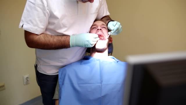 Young man at dentist, panning shot video