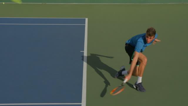 若い男のバックハンドをスローモーションで返します。 - テニス点の映像素材/bロール