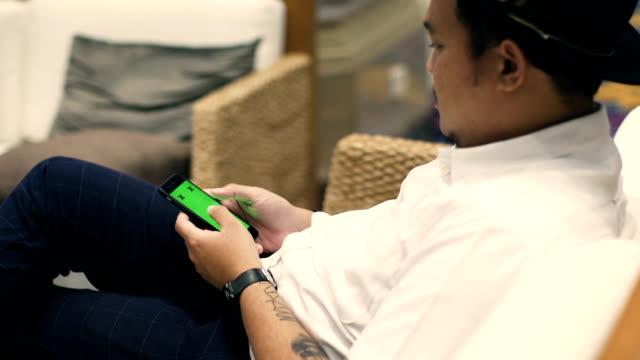 ung man tom smartphone chroma key - telefonmeddelande bildbanksvideor och videomaterial från bakom kulisserna