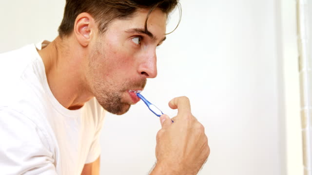 Young man brushing his teeth with toothbrush in the bathroom 4K 4k video