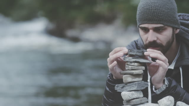 Young man building tower of rocks by the river. Looking for balance video
