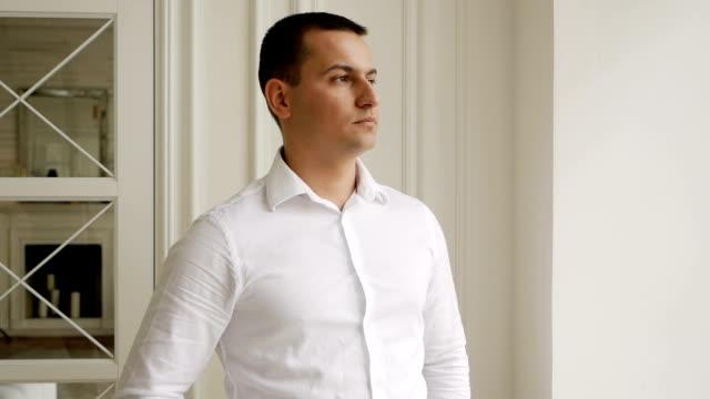 jeune homme d'affaires dans une chemise blanche se dresse à la fenêtre - Vidéo