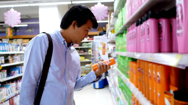hombre joven comprar champú en centro comercial - vídeo