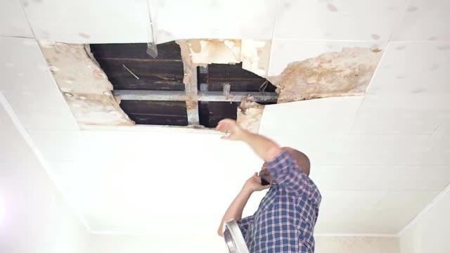ung man ringa på telefonen i tjänsten och allmännyttiga företag. takpaneler skadad stort hål i taket från regnvatten läckage. vattenskadade tak, försäkring fall. - skada bildbanksvideor och videomaterial från bakom kulisserna