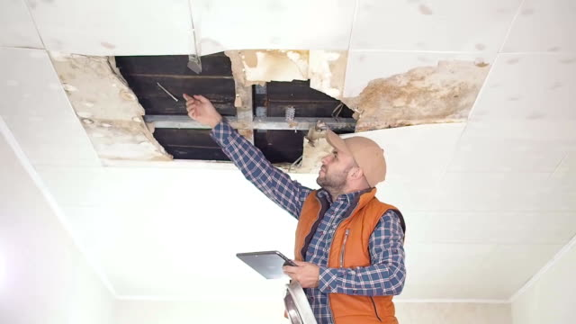 Young man call on the phone in the Service, and public utilities. Ceiling panels damaged huge hole in roof from rainwater leakage.Water damaged ceiling , Insurance case. video