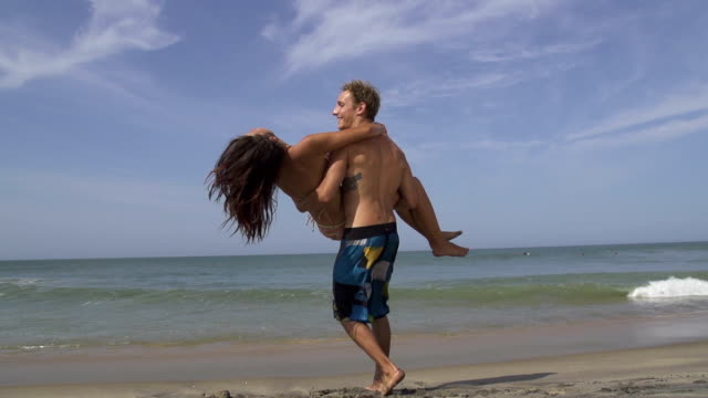 SLOW MOTION: Young man carrying his girlfriend on the beach video