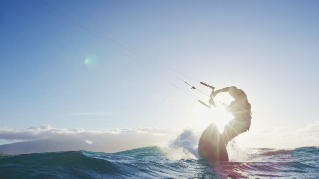 Young man catches air kite surfing. Extreme kite boarding in slow motion.