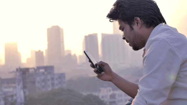 a young man checking his phone against the vibrant city skyline - india video stock e b–roll