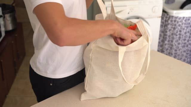 A young man chooses a zero waste lifestyle A young man chooses a zero waste lifestyle. Waste Reduction and Reducing. Reusable cloth produce bag. Plastic alternatives for food packaging canvas fabric stock videos & royalty-free footage