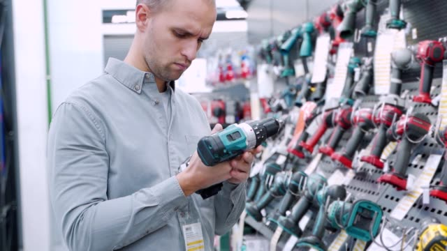 A young man chooses cordless screwdriver in the hardware store A young man chooses cordless screwdriver in the hardware store. cordless phone stock videos & royalty-free footage