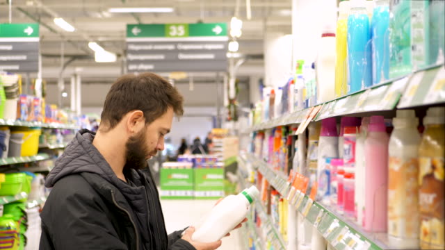young man chooses household chemicals in the supermarket. 4k uhd - lysol stock videos & royalty-free footage
