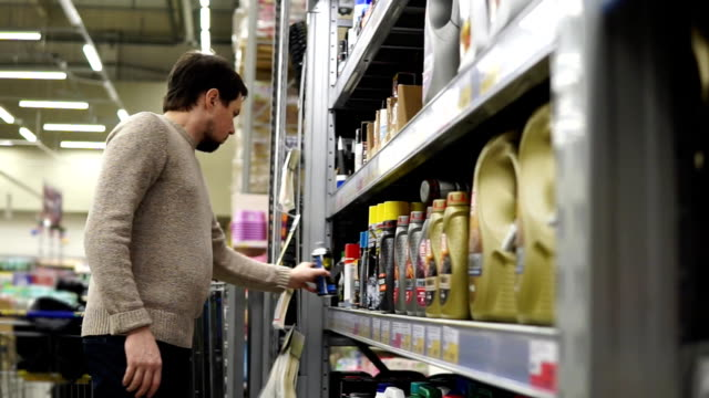 Young man choosing lubricant for his car video