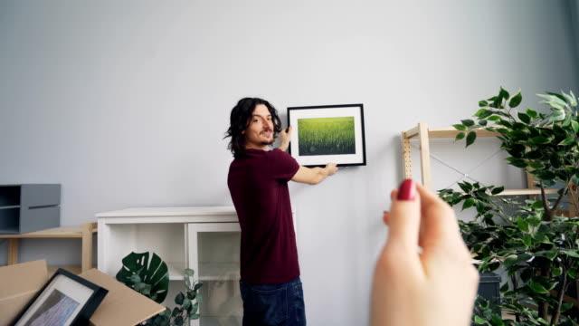 ung man väljer plats för bild medan flickvän hjälpa honom göra en gest - fotoram bildbanksvideor och videomaterial från bakom kulisserna