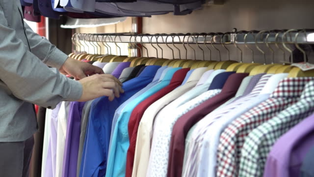 young man choosing shirt in the clothing store - abbigliamento elegante video stock e b–roll