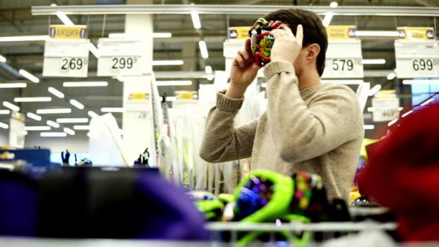 young man choosing snowboard glasses in the hypermarket - negozio sci video stock e b–roll