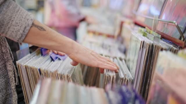 レコードショップでヴィンテージビニールlpを選択する若者 - アナログレコード点の映像素材/bロール
