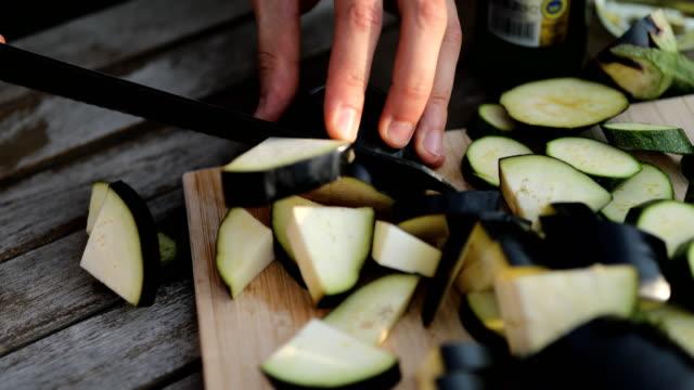 vídeos y material grabado en eventos de stock de hombre joven de berenjena para picar en la tabla de cortar - cortar en trozos preparar comida